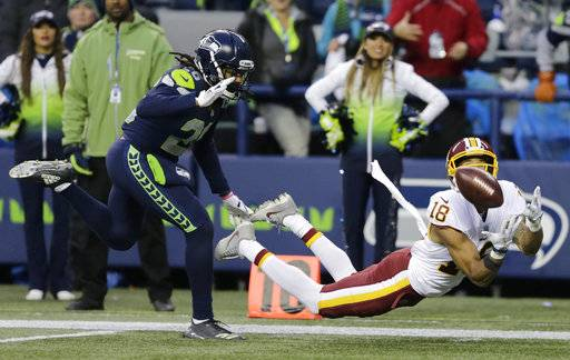 FILE - In this Sunday, Nov. 5, 2017, file photo, Washington Redskins wide receiver Josh Doctson, right, makes a diving catch ahead of Seattle Seahawks cornerback Shaquill Griffin, left, in the second half of an NFL football game in Seattle. The Redskins won 17-14. Injuries to Jordan Reed and Jamison Crowder put Terrelle Pryor and Josh Doctson front and center for Washington Redskins quarterback Kirk Cousins. Maybe it was just what Cousins needed to develop chemistry with new receivers.