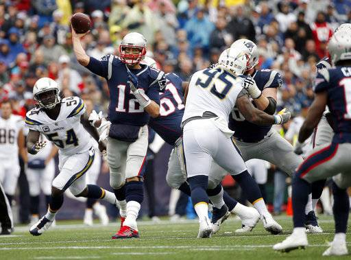 FILE - In this Oct. 29, 2017, file photo, New England Patriots quarterback Tom Brady (12) passes under pressure from Los Angeles Chargers linebacker Melvin Ingram (54) and defensive end Tenny Palepoi (95) during the first half of an NFL football game in Foxborough, Mass. John Elway has measured the Broncos' success against the Patriots both on and off the football field since taking over as head of football operations in 2011. Either the Patriots or Broncos have earned the AFC's top playoff seed every year since with the Patriots winning three conference championships and two Super Bowls and the Broncos winning two AFC titles and one Super Bowl.