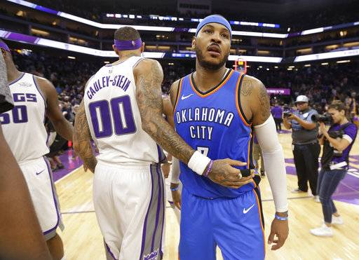 Sacramento Kings center Willie Cauley-Stein, left, and Oklahoma City Thunder forward Carmelo Anthony pass each other after the Kings defeated the Thunder 94-86 in an NBA basketball game Tuesday, Nov. 7, 2017, in Sacramento, Calif.