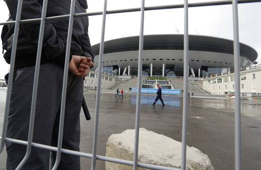 FILE - In this file photo dated Saturday, Sept. 10, 2016, a security man stands guard at the soccer stadium on Krestovsky Island which will host some 2018 World Cup matches, under construction in St.Petersburg, Russia.  A court in St. Petersburg said Wednesday Nov. 8, 2017, a former deputy governor of St. Petersburg, Marat Oganesya, has admitted a fraud charge related to the construction of the city's 2018 World Cup stadium.