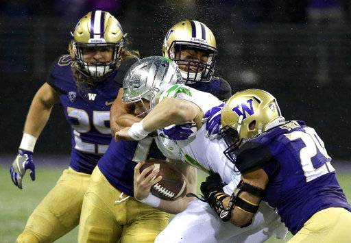 FILE - In this Nov. 4, 2017, file photo, Oregon quarterback Braxton Burmeister is tackled by Washington linebackers Connor O'Brien, right, and Brandon Wellington, upper center, as linebacker Ben Burr-Kirven, left, looks on in the first half of an NCAA college football game in Seattle. Pete Kwiatkowski is the defensive coordinator for No. 9 Washington, which brings the best defense in the country into Friday's matchup at Stanford. Kwiatkowski is quiet an unassuming. His players see him differently.