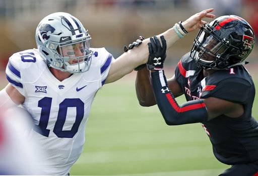 FILE - In this Saturday, Nov. 4, 2017, file photo, Kansas State quarterback Skylar Thompson (10) pushes off of Texas Tech's Jordyn Brooks (1) during an NCAA college football game in Lubbock, Texas. Thompson, Kansas State's third-string quarterback, came off to bench to lead the Wildcats to a 42-35 overtime win last Saturday over Texas Tech. Kansas State plays West Virginia on Saturday, Nov. 11, in Manhattan, Kansas. (Brad Tollefson/Lubbock Avalanche-Journal via AP, File)