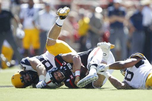 FILE - In this Oct. 15, 2016, file photo, Texas Tech quarterback Patrick Mahomes II is tackled by West Virginia defensive lineman Reese Donahue, left, and safety Kyzir White (8) in the second quarter of an NCAA college football game in Lubbock, Texas. Donahue has 16 tackles over his last three games to nearly double his season total and is part of a defensive line that is winning praise from West Virginia defensive coordinator Tony Gibson. (Mark Rogers/Lubbock Avalanche-Journal via AP, File)