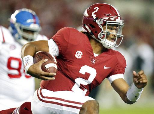 FILE- In this Sept. 30, 2017, file photo, Alabama quarterback Jalen Hurts runs the ball against Mississippi during the first half of an NCAA college football game in Tuscaloosa, Ala. The Southeastern Conference doesn't have any players putting up video game-style numbers. But, there's plenty of big games left for players like Hurts and Georgia's Nick Chubb to produce Heisman moments.
