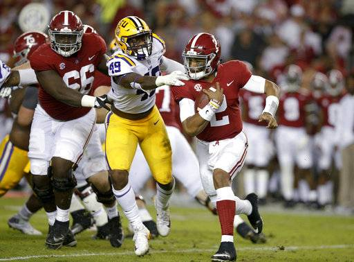 Alabama quarterback Jalen Hurts carries the ball before being tackled by LSU linebacker Arden Key during the first half of an NCAA college football game, Saturday, Nov. 4, 2017, in Tuscaloosa, Ala.