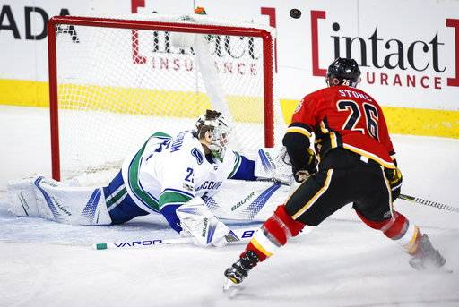 Vancouver Canucks goalie Jacob Markstrom, left, from Sweden, deflects the puck over the net as Calgary Flames' Michael Stone watches during the second period of an NHL hockey game Tuesday, Nov. 7, 2017, in Calgary, Alberta. (Jeff McIntosh/The Canadian Press via AP)