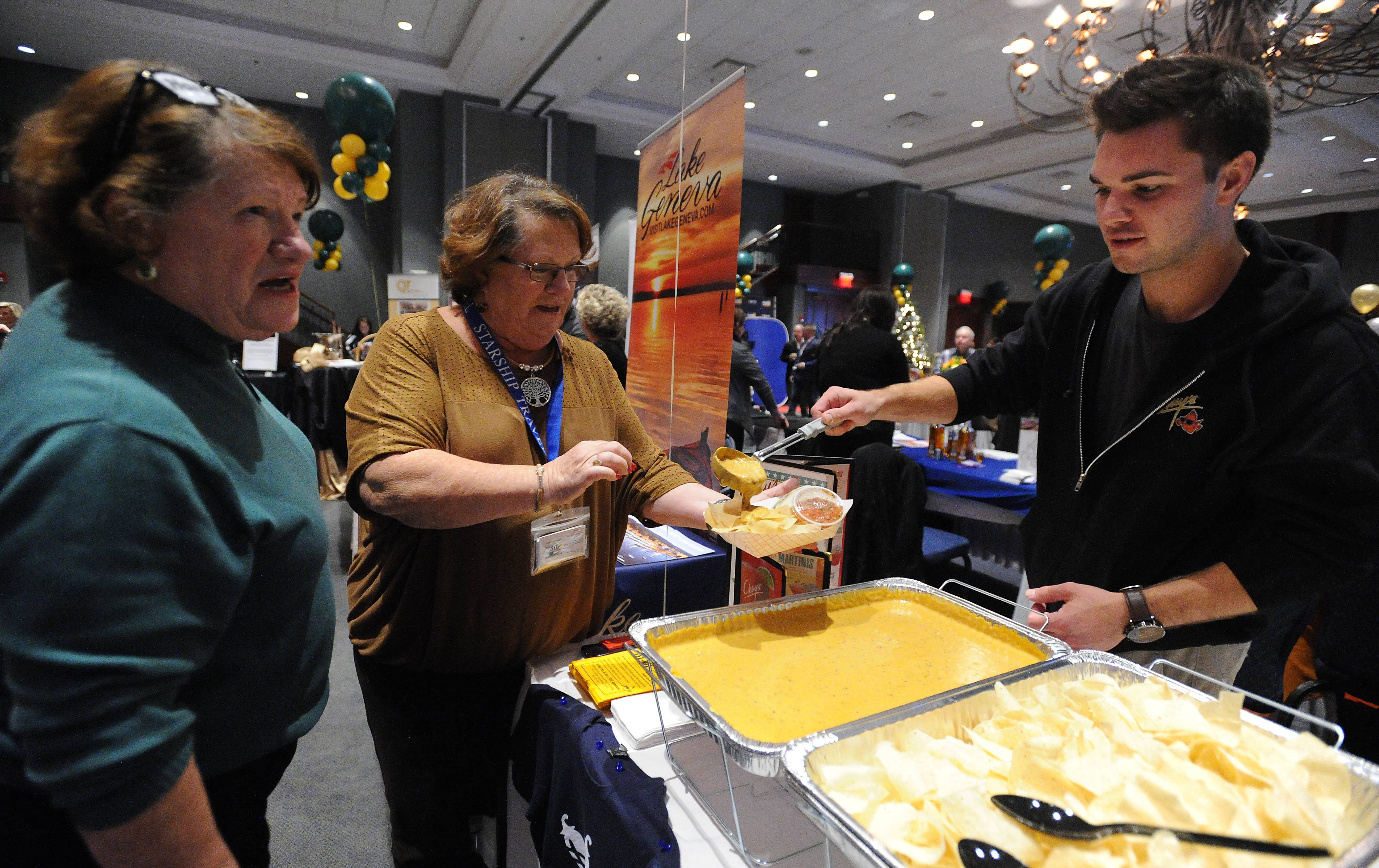 Mark Welsh/mwelsh@dailyherald.comLinda Schreiber (left) of Arlington Heights along with her sister Karen Kass samples food from the new Schaumburg restaurant Chuys's by Anthony Klebba at the Daily Herald Business Ledger Hospitality Expo Northwest in Hoffman Estates on Thursday.