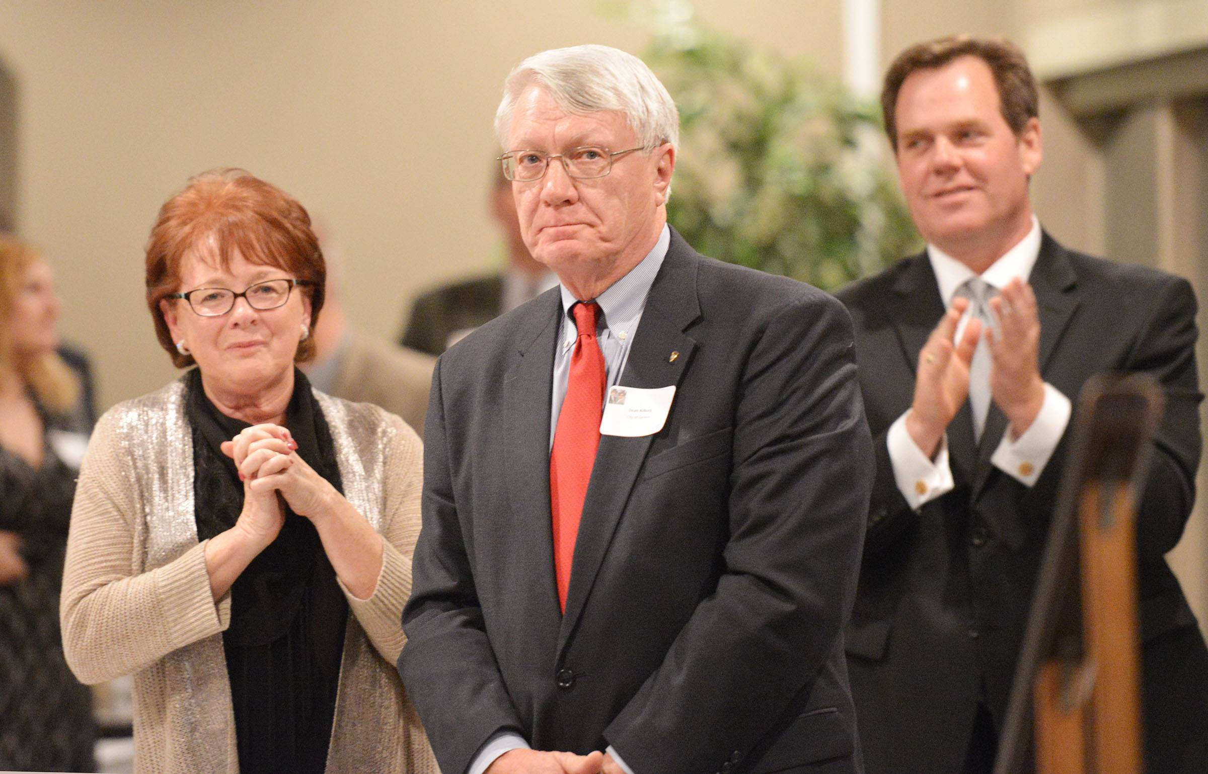 Dean Kilburg stands with his wife, Linda, and is applauded by Geneva Mayor Kevin Burns at the Geneva Chamber of Commerce banquet Thursday night. He received the prestigious Wood Community Service Award.