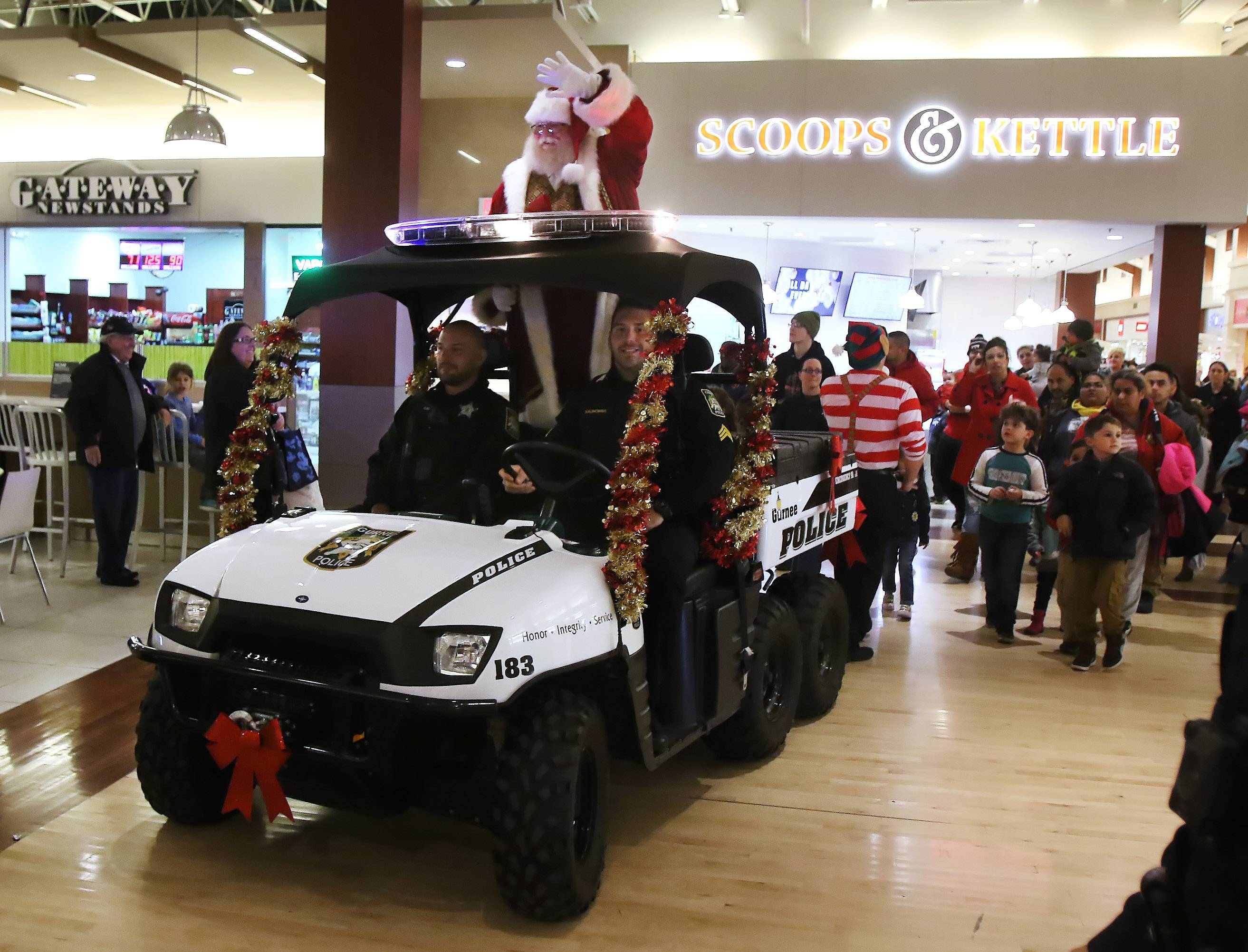 During Santa's Arrival Parade on Thursday evening at Gurnee Mills, Santa navigated through the mall in a police ATV followed by a throng of children and their parents.