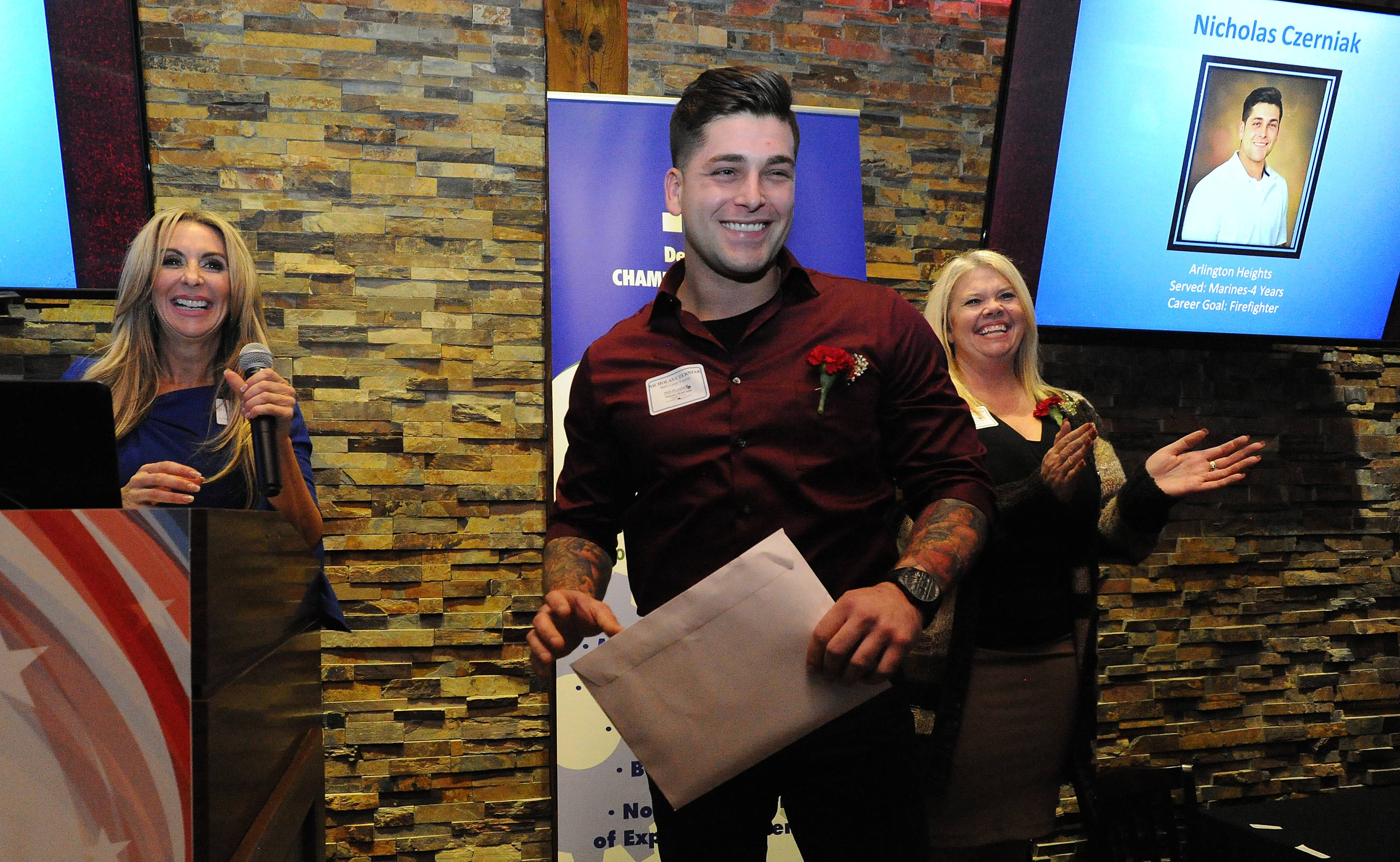 Andrea Biwer, executive director of the chamber of commerce, left, and Marne Deithorn, with the Rivers Casino human resources department honor Nicholas Czerniak of Arlington Heights, who served in the Marines, at the Des Plaines Chamber of Commerce Veterans ceremony in Rosemont Thursday.