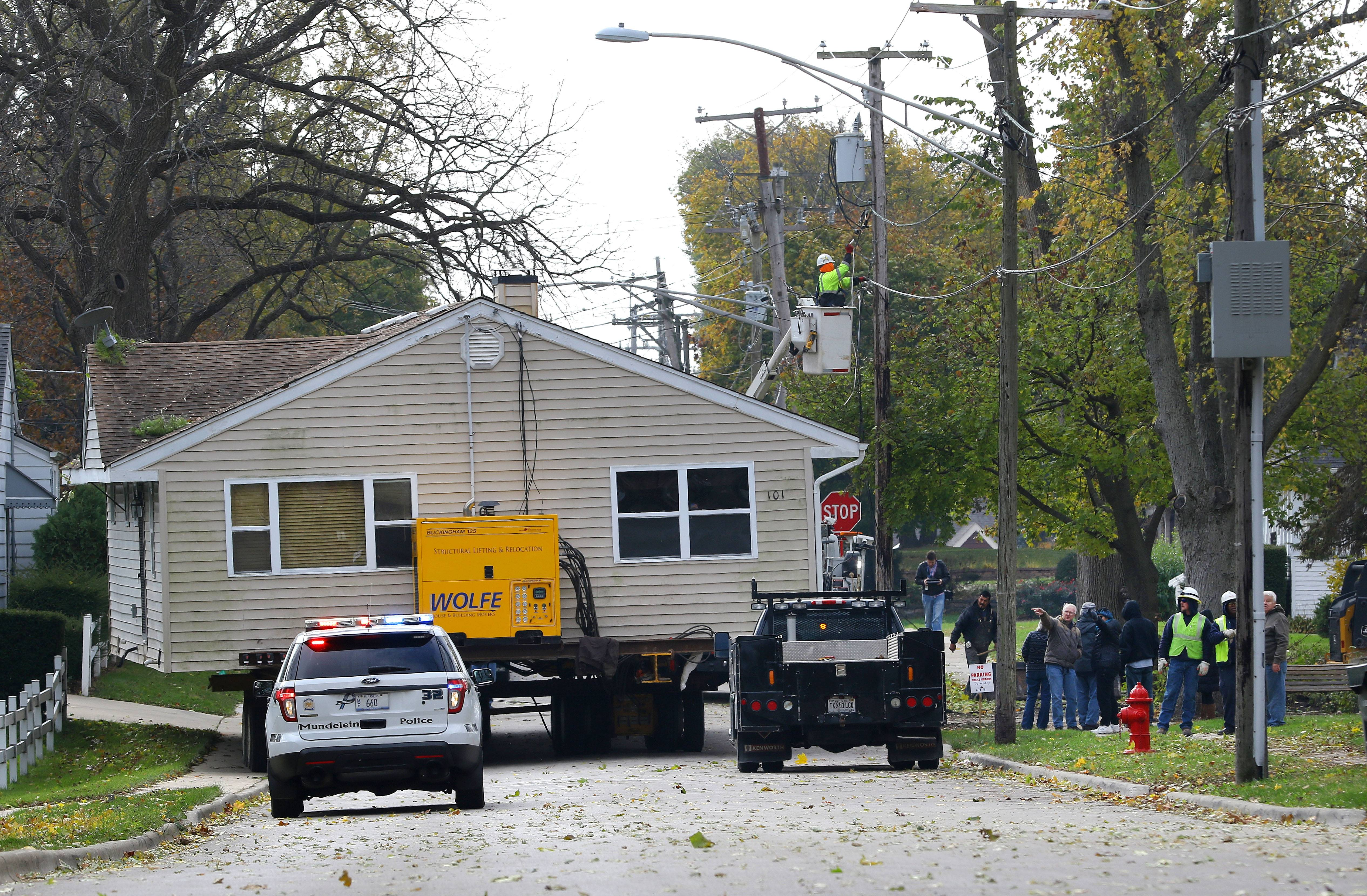 Utility workers lower lines as a three-bedroom Mundelein house is moved to its new lot in the village at 516 N. Prairie Ave. The house, moved to make way for a stormwater project, was placed on a lot where a dilapidated structure was torn down two weeks ago.