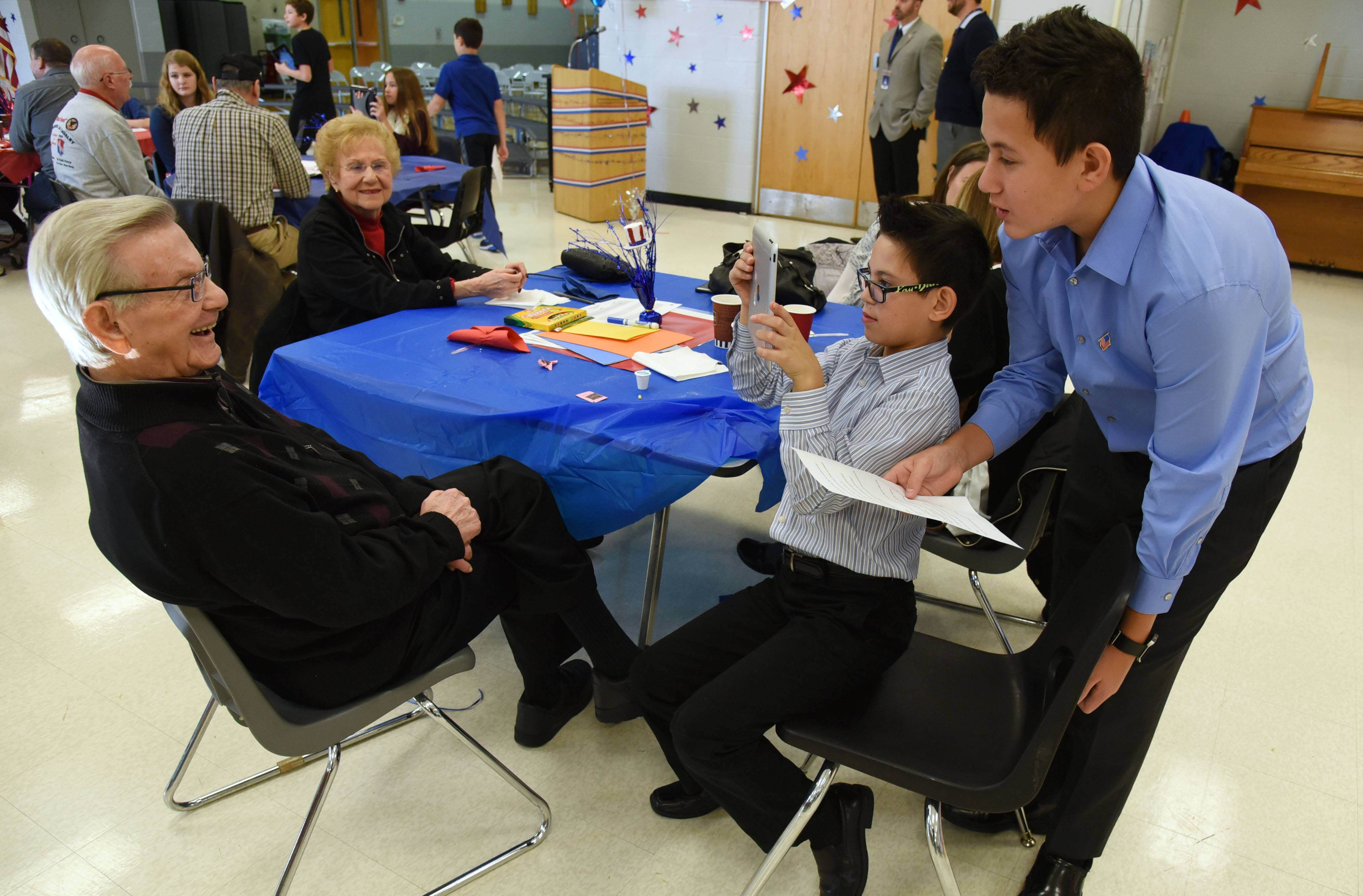 World War II Air Force veteran Max Sokol, left, of Glenview is interviewed by his great grandsons Ethan Espina, right, and Tyler Espina during the Hawthorn Middle School South's annual Veterans Day Breakfast Thursday in Vernon Hills. Students interviewed the visiting veterans about their experiences while serving in the military.