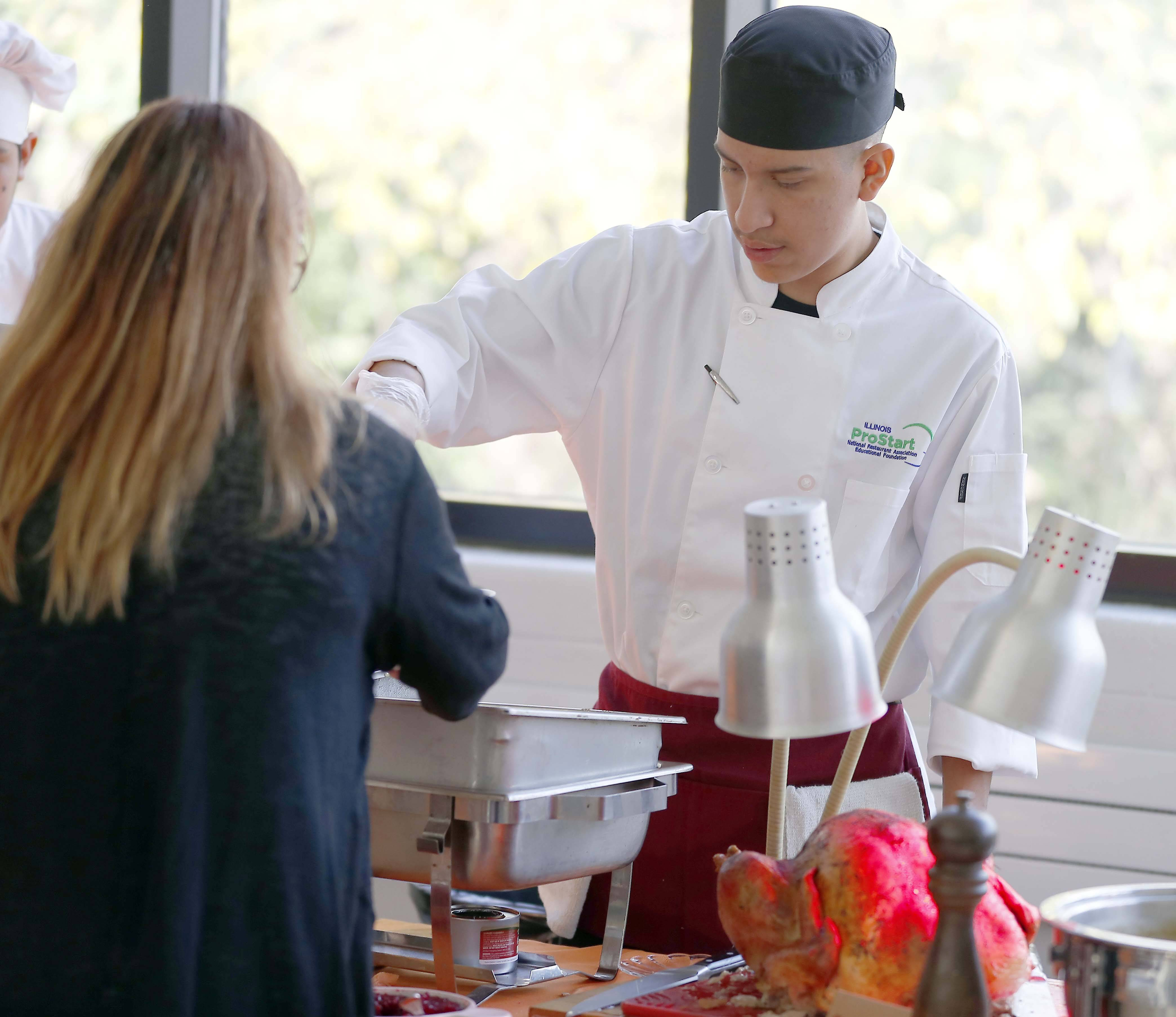 Brian Onofre, 17, a student in Elgin High School's Clumsy Chef culinary program, and classmates prepared and served a fall feast Thursday at the school.