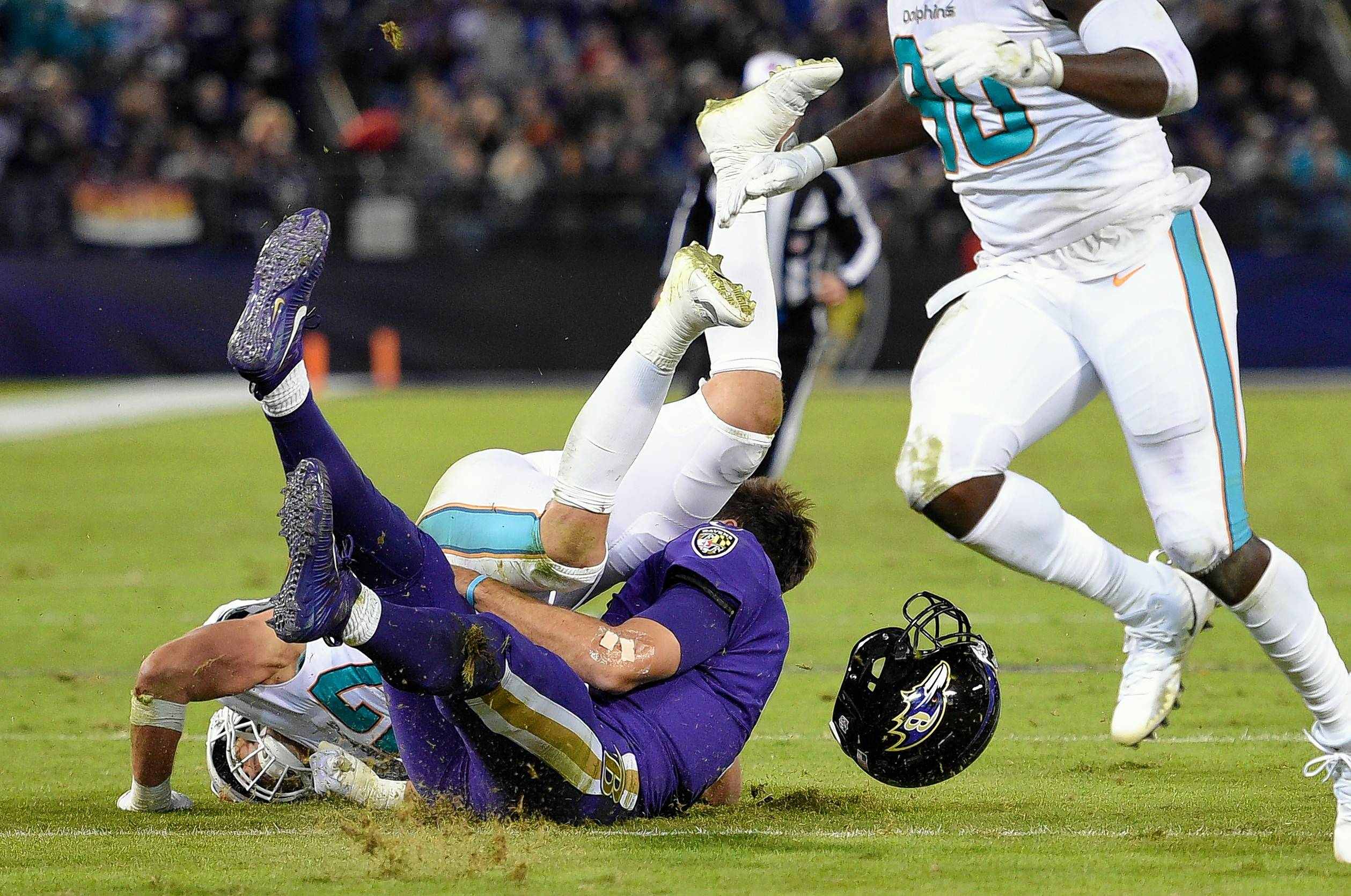 Miami Dolphins middle linebacker Kiko Alonso, top left, colliding with Baltimore Ravens quarterback Joe Flacco in the first half in Baltimore. Flacco missed the rest of the game, but cleared concussion protocol.