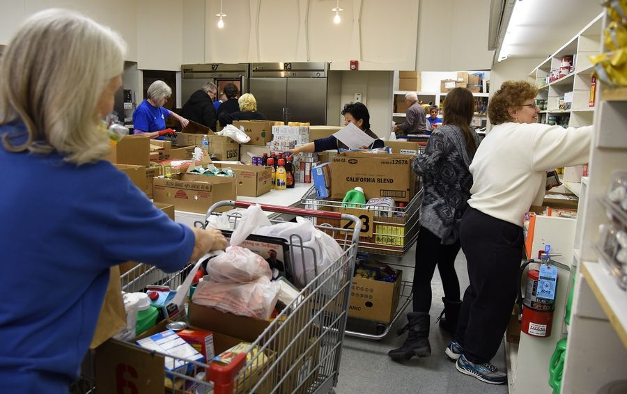 Volunteers fill shopping carts for people in need at the FISH Food Pantry in Carpentersville.
