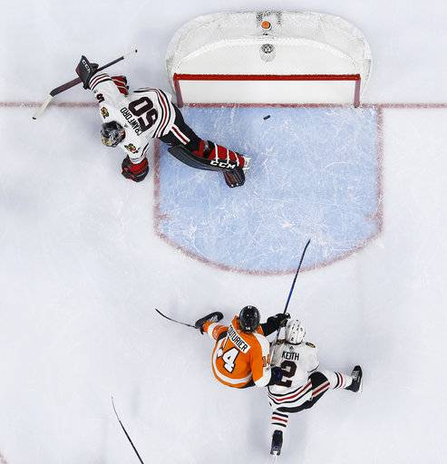 Philadelphia Flyers' Sean Couturier (14) scores a goal past Chicago Blackhawks' Corey Crawford (50) as Duncan Keith (2) defends during the second period of an NHL hockey game, Thursday, Nov. 9, 2017, in Philadelphia.