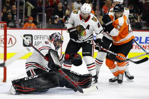 Chicago Blackhawks' Corey Crawford, left, blocks a shot as teammate Duncan Keith, center, and Philadelphia Flyers' Shayne Gostisbehere look for a rebound during the second period of an NHL hockey game, Thursday, Nov. 9, 2017, in Philadelphia.