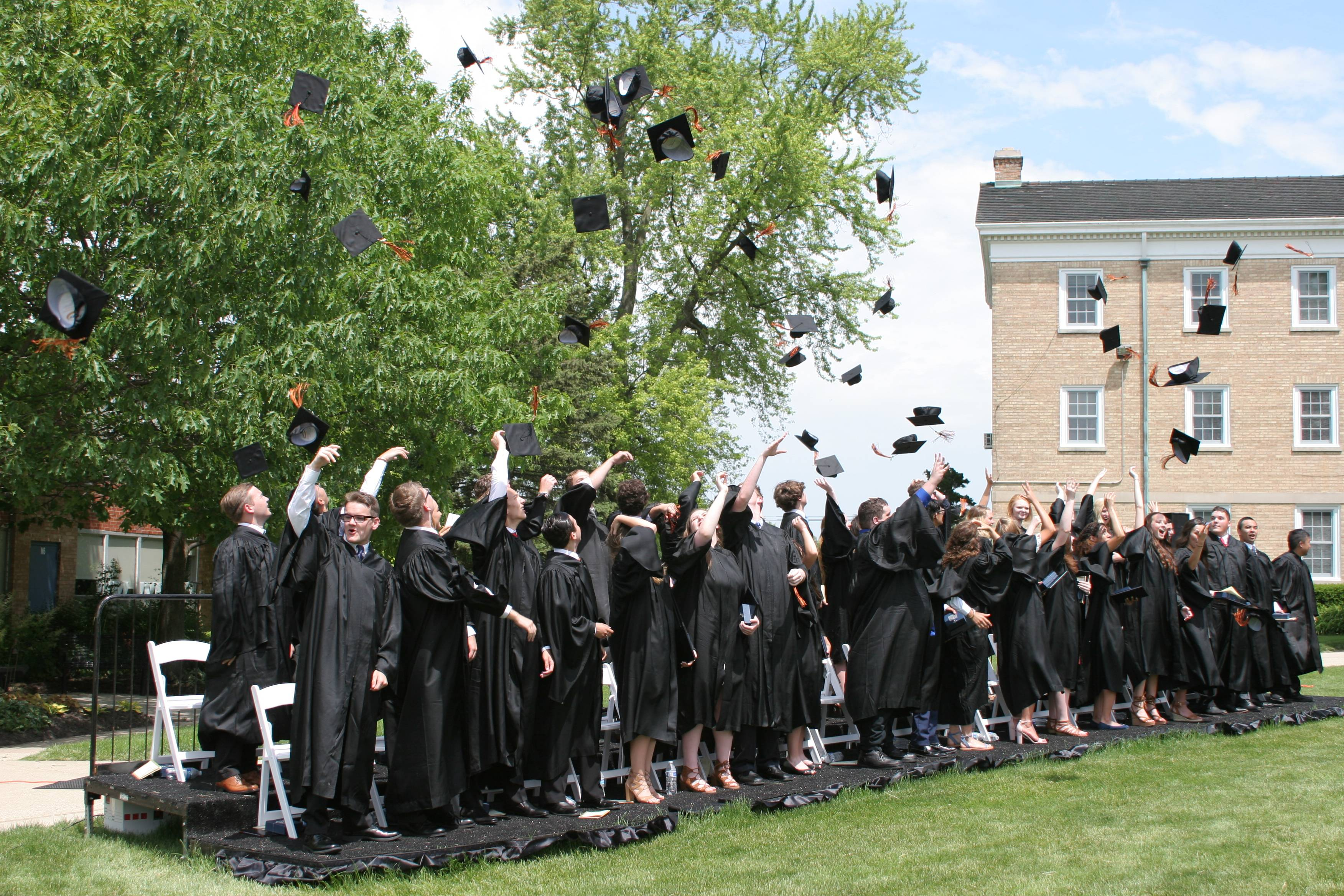The 2017 Elgin Academy graduates throw their mortarboards in the air. Elgin Academy is offering Hilltopper Merit-Based Scholarships for 2018-19.