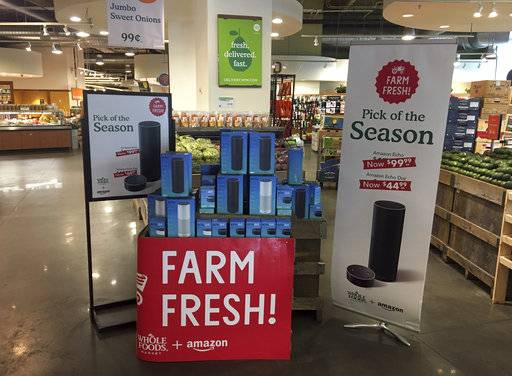 FILE - In this Monday, Aug. 28, 2017, file photo, Amazon's Echo and Echo Dot appear on sale at a Whole Foods Market in New York. You may see more of Amazon inside Whole Foods soon: The online retailer, which has been already been selling its voice-activated Echos at Whole Foods, will start to sell Kindles, Fire tablets and other Amazon devices at its grocery stores.