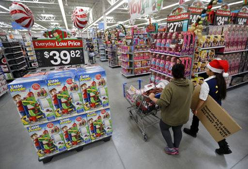 FILE - In this Wednesday, Oct. 26, 2016, file photo, a shopper, left, walks with a store associate in the toy section at Walmart in Teterboro, N.J. Walmart hopes to tempt shoppers with online deals before Black Friday. It's beginning some online deals Thursday and plans to offer most of its Black Friday deals online starting at 12:01 a.m. on Thanksgiving.
