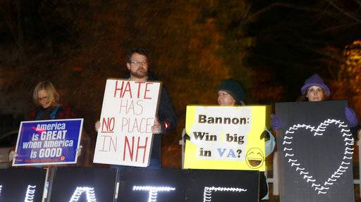 Protesters hold signs ahead of an event featuring Steve Bannon, the former chief strategist to President Donald Trump, in Manchester, N.H., Thursday, Nov. 9, 2017.