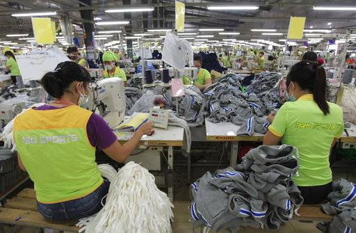 In this Oct. 24, 2017, photo, garment workers sew clothes at Pro Sports factory in Nam Dinh province, Vietnam. U.S. President Donald Trump's decision to withdraw from a far-reaching Pacific Rim trade pact is having scant impact on fast-growing trade in the region.
