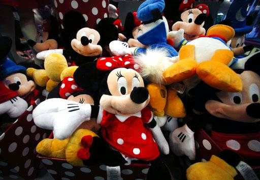 FILE - This Jan. 31, 2014, file photo shows plush Disney characters piled up in a display at a Disney Store in Saugus, Mass. The Walt Disney Co. reports financial results on Thursday, Nov. 9, 2017.
