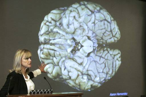 Ann McKee, director Boston University's center for research into the degenerative brain disease chronic traumatic encephalopathy, or CTE, addresses an audience on the school's campus Thursday, Nov. 9, 2017 about the study of NFL football player Aaron Hernandez's brain, projected on a screen behind, in Boston. McKee says Hernandez suffered severe damage to parts of the brain that play an important role in memory, impulse control and behavior.