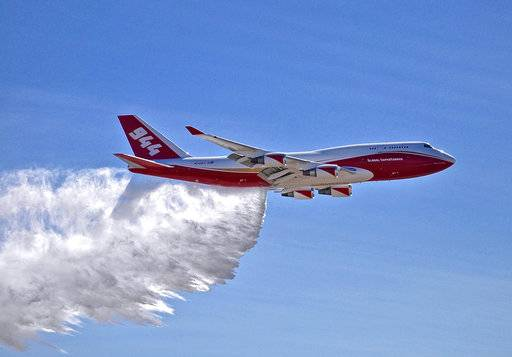 FILE - This May 5, 2016, file photo provided by Global Supertanker Services shows a Boeing 747 making a demonstration water drop at Colorado Springs Airport in Colorado Springs, Colo. The giant passenger jet converted to fight wildfires but grounded by U.S. officials during much of this year's fire season could be aloft much more next year. The U.S. Government Accountability Office on Thursday, Nov. 9, 2017, sided with Global SuperTanker Services in its protest against the U.S. Forest Service. The Colorado-based company challenged the Forest Service's 5,000-gallon (19,000-liter) limit on air tankers that kept the 19,000-gallon (72,000-liter) Boeing 747-400 idle until late August. After that it flew only in California. (Hiroshi Ando/Global Super Tanker Services LLC via AP, File)