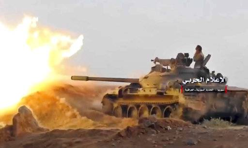 This frame grab from video provided Wednesday, Nov 8, 2017, by the government-controlled Syrian Central Military Media, shows a tank firing on militants' positions on the Iraq-Syria border. The United States and Russia are nearing an agreement on Syria for how they hope to resolve the Arab country's civil war once the Islamic State group is defeated, officials said Nov. 9. (Syrian Central Military Media, via AP)