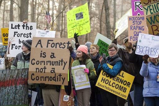 "Protestors gather at the Yellowwood State Forest office near Belmont, Ind. Thursday, Nov. 9, 2017 to protest the timber sale of more than 1,700 trees in old growth areas of the forest. Protestors yell ""Shame on you"" as loggers make their way into the sale. (Chris Howell/The Herald-Times via AP)"