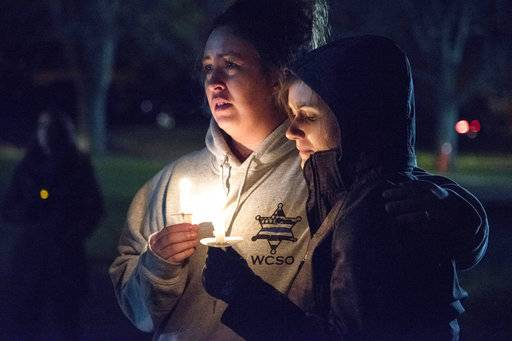 "In this Nov. 6, 2017 photo community members listen to prayers read at a vigil in honor of fallen Rockford police officer Jaimie Cox in Rockford, Ill. Cox died during a traffic stop Sunday, Nov. 5, 2017 in Rockford, Ill. Authorities say Cox and another man were both found dead at the scene of a single-vehicle crash. Rockford police Chief Dan O'Shea says Cox became ""entangled"" with the car and fired a shot, but he declined to say how either man died or to provide additional details. (Kayli Plotner/Rockford Register Star via AP)"