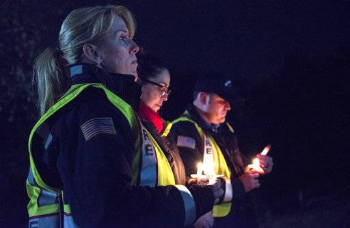 "In this Nov. 6, 2017 photo members of the Rockford Fire Department listen to prayers read at a vigil in honor of fallen Rockford police officer Jaimie Cox in Rockford, Ill. Cox died during a traffic stop Sunday, Nov. 5, 2017 in Rockford, Ill. Authorities say Cox and another man were both found dead at the scene of a single-vehicle crash. Rockford police Chief Dan O'Shea says Cox became ""entangled"" with the car and fired a shot, but he declined to say how either man died or to provide additional details. (Kayli Plotner/Rockford Register Star via AP)"