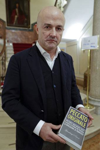"Journalist Gianluigi Nuzzi holds a copy of his latest book ""Peccato Originale"" (Original Sin) as he poses for photos during a press conference to present it, in Rome, Thursday, Nov. 9, 2017."