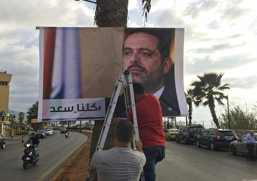 "Workers hang a poster of outgoing Prime Minister Saad Hariri with Arabic words that read, ""We are all Saad,"" on a seaside street in Beirut, Lebanon, Thursday, Nov. 9, 2017. Hezbollah has called on Saudi Arabia to stay out of Lebanese affairs, saying the resignation of Prime Minister Saad Hariri, announced from Riyadh over the weekend, ""has raised many questions."" (AP Photo/Hussein Malla)"
