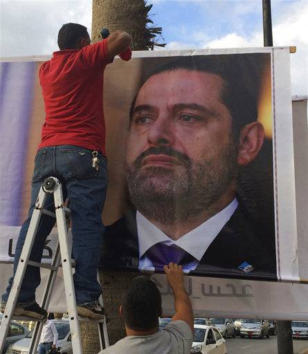 "Workers hang a poster of outgoing Prime Minister Saad Hariri with Arabic words that read, ""We are all Saad,"" on a seaside street in Beirut, Lebanon, Thursday, Nov. 9, 2017. Hezbollah has called on Saudi Arabia to stay out of Lebanese affairs, saying the resignation of Prime Minister Saad Hariri, announced from Riyadh over the weekend, ""has raised many questions."""