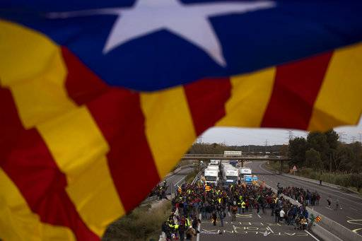 Demonstrators block a highway during a general strike in Borrassa, near Girona, Spain, Wednesday, Nov. 8, 2017. A general strike in Catalonia was muted Wednesday, but pro-independence protesters blocked roads and stopped trains in Spain's northeastern region to protest the jailing of ousted Catalan government officials and secessionist activists.