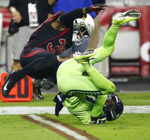 Seattle Seahawks wide receiver Paul Richardson makes the catch as Arizona Cardinals safety Budda Baker, left, defends during the first half of an NFL football game, Thursday, Nov. 9, 2017, in Glendale, Ariz.