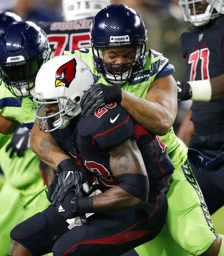 Arizona Cardinals running back Adrian Peterson (23) is stopped by Seattle Seahawks defensive end Michael Bennett during the first half of an NFL football game, Thursday, Nov. 9, 2017, in Glendale, Ariz.
