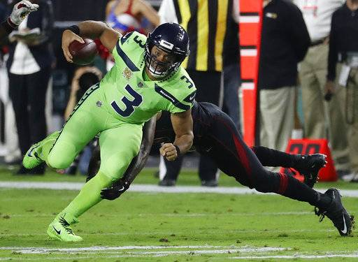 Seattle Seahawks quarterback Russell Wilson (3) eludes the tackle agasint the Arizona Cardinals during the first half of an NFL football game, Thursday, Nov. 9, 2017, in Glendale, Ariz.