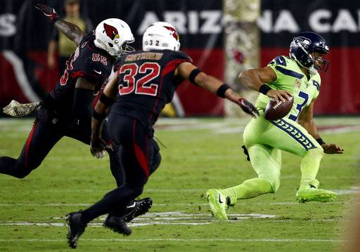 Seattle Seahawks quarterback Russell Wilson (3) scrambles as Arizona Cardinals free safety Tyrann Mathieu (32) and outside linebacker Chandler Jones (55) pursue during the second half of an NFL football game, Thursday, Nov. 9, 2017, in Glendale, Ariz.