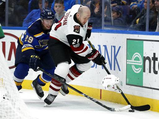 Arizona Coyotes' Derek Stepan (21) loses his helmet while reaching for a loose puck with St. Louis Blues' Vince Dunn (29) during the third period of an NHL hockey game Thursday, Nov. 9, 2017, in St. Louis. The Blues won 3-2 in a shootout.
