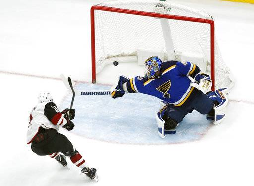 Arizona Coyotes' Brendan Perlini, left, scores past St. Louis Blues goalie Carter Hutton during the second period of an NHL hockey game Thursday, Nov. 9, 2017, in St. Louis.