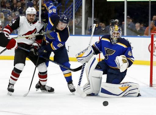Arizona Coyotes' Zac Rinaldo, left, and St. Louis Blues goalie Carter Hutton, right, and Blues' Vince Dunn watch the puck during the first period of an NHL hockey game Thursday, Nov. 9, 2017, in St. Louis.