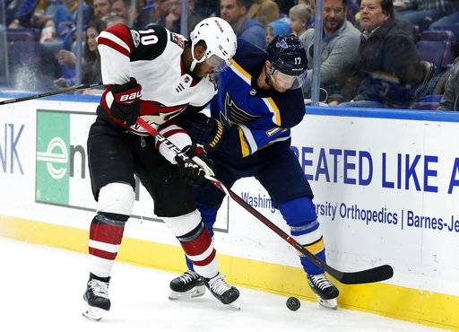 Arizona Coyotes' Anthony Duclair (10) and St. Louis Blues' Jaden Schwartz chase the puck along the boards during the first period of an NHL hockey game Thursday, Nov. 9, 2017, in St. Louis.