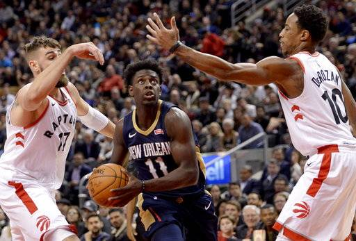 New Orleans Pelicans guard Jrue Holiday (11) drives to the net between Toronto Raptors center Jonas Valanciunas (17) andDeMar DeRozan (10) during the second half of an NBA basketball game Thursday, Nov. 9, 2017, in Toronto. (Nathan Denette/The Canadian Press via AP)