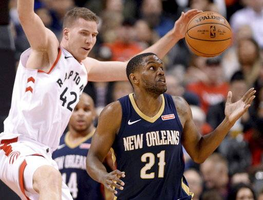 New Orleans Pelicans forward Darius Miller (21) and Toronto Raptors center Jakob Poeltl (42) watch the ball during the second half of an NBA basketball game Thursday, Nov. 9, 2017, in Toronto. (Nathan Denette/The Canadian Press via AP)