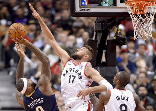 New Orleans Pelicans center DeMarcus Cousins (0) gets blocked by Toronto Raptors centre Jonas Valanciunas (17) as Toronto's Serge Ibaka (9) watches during the first half of an NBA basketball game Thursday, Nov. 9, 2017, in Toronto. (Nathan Denette/The Canadian Press via AP)