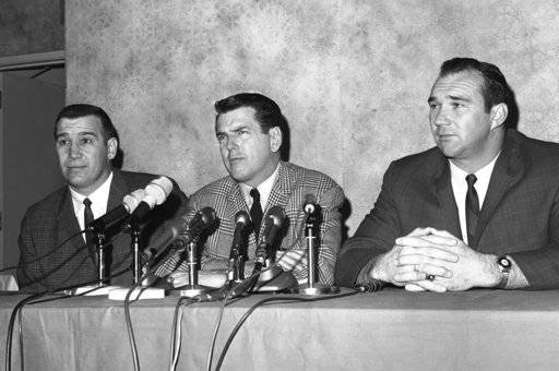 FILE - In this January 1966 file photo, George Allen, defensive coach of the Chicago Bears who was hired as head coach of the Los Angeles Rams, is flanked by two Bear defensive stars, Joe Fortunato, left, and Doug Atkins, at a Los Angeles news conference announcing his new job in Los Angeles. Fortunate and Atkins, staying at the hotel where the conference took place, dropped in to voice approval of Allen's ability. Fortunato, the speedy linebacker who helped the Bears win the 1963 NFL title, has died. He was 87. Fortunato died Monday, Nov. 6, 2017, in Mississippi, where he starred at linebacker and fullback at Mississippi State.