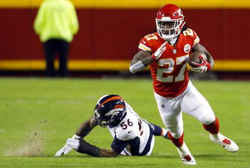 FILE - In this Oct. 30, 2017, file photo, Kansas City Chiefs running back Kareem Hunt (27) runs past a tackle attempt by Denver Broncos linebacker Shane Ray (56) during the first half of an NFL football game in Kansas City, Mo. Hunt, a third-round pick out of Toledo, of all places, leads the league in rushing with 800 yards.